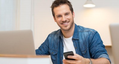 young man by laptop smiling at camera with phone in hand