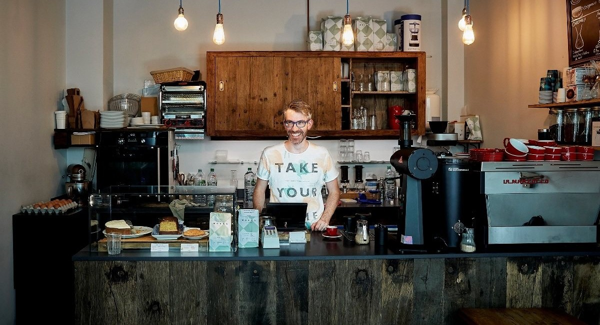 man standing behind cafe counter with tablet POS