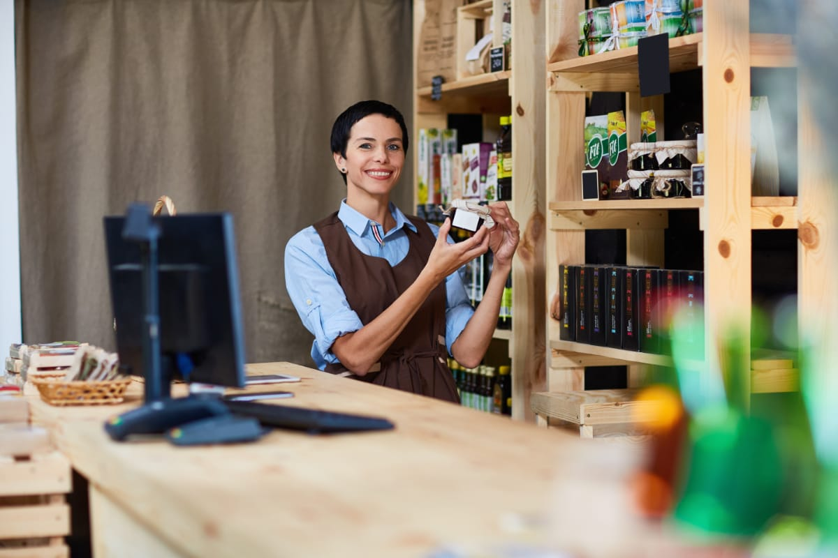 Till assistant smiling with product behind counter